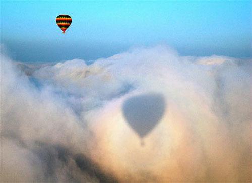"""Глория. Когда свет подвергается эффекту обратного рассеивания (дифракция света, ранее уже отраженного в водяных кристаллах облака), он возвращается от облака в том же направлении, по которому падал, и образует эффект, получивший название """"Глория"""". Наблюдать этот эффект можно только на облаках, которые находятся прямо перед зрителем или ниже его, в точке, которая находится на противоположной стороне к источнику света. Таким образом, увидеть Глорию можно только с горы или из самолета, причем источники света (Солнце или Луна) должны находиться прямо за спиной наблюдателя. Радужные круги Глории в Китае еще называют Светом Будды. На этой фотографии прекрасный радужный ореол окружает тень воздушного шара, упавшую на находящееся ниже него облако."""