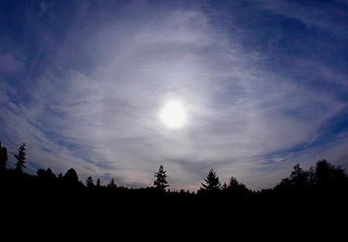"""Гало в 22º. Белые световые окружности вокруг Солнца или Луны, которые возникают в результате преломления или отражения света находящимися в атмосфере кристаллами льда или снега, называются гало. В атмосфере присутствуют небольшие кристаллы воды, и когда их грани образуют прямой угол с плоскостью, проходящей через Солнце, того, кто наблюдает эффект, и кристаллы, на небе становится виден характерный белый ореол, окружающий Солнце. Так грани отражают лучи света с отклонением на 22°, образуя гало. В холодное время года гало, образованные кристаллами льда и снега на поверхности земли, отражают солнечный свет и рассеивают его в разных направлениях, образуя эффект под названием """"бриллиантовая пыль""""."""