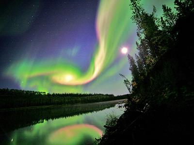 Северное полярное сияние горит в небе над городом Уайтхорс, территория Юкон, Канада. (David Cartier, Sr./NASA via Reuters)
