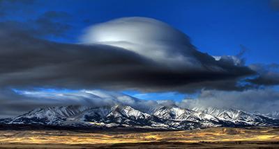 Лентикулярное облако образовалось над горами в штате Монтана, США. (James Woodcock, Billings Gazette via Associated Press)