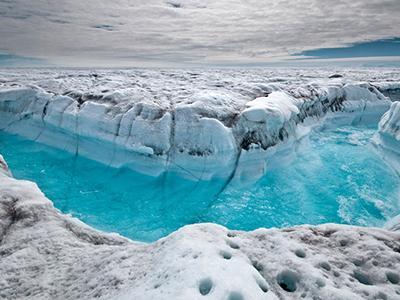 Талая вода бежит по траншее, вымытой в поверхности Гренландского ледяного щита, к юго-западу от Илулиссата, Гренландия. (Ian Joughin/Associated Press)